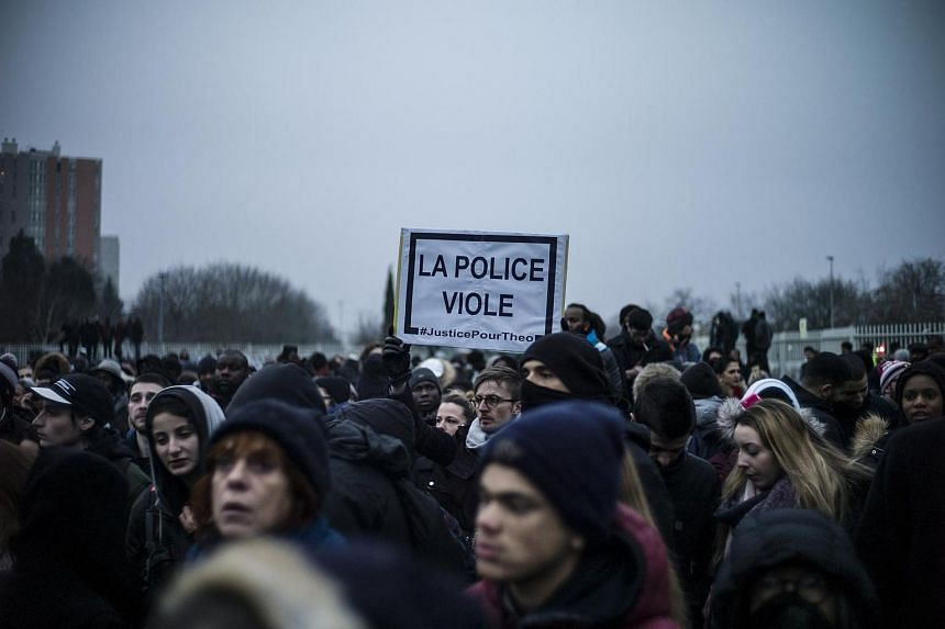 A man holds a banner reading 'Police rapes' in Bobigny, a suburb of Paris, France, on Feb 11, 2017.