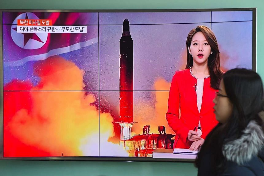 A woman walks past a television screen showing file footage of North Korea's missile launch at a railway station in Seoul on Feb 12, 2017.