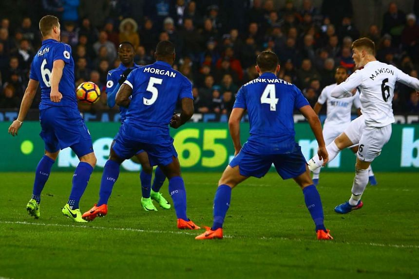 Swansea City's English defender Alfie Mawson (right) shoots to score the opening goal of the English Premier League football match between Swansea City and Leicester City on Feb 12, 2017.