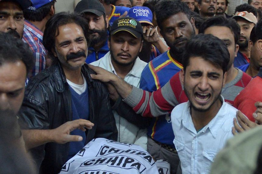 Relatives and colleagues mourn around the body of Taimoor Abbas, an employee of a Pakistani TV news channel, who was shot dead while reporting on an assault in Karachi on Feb 12, 2017.