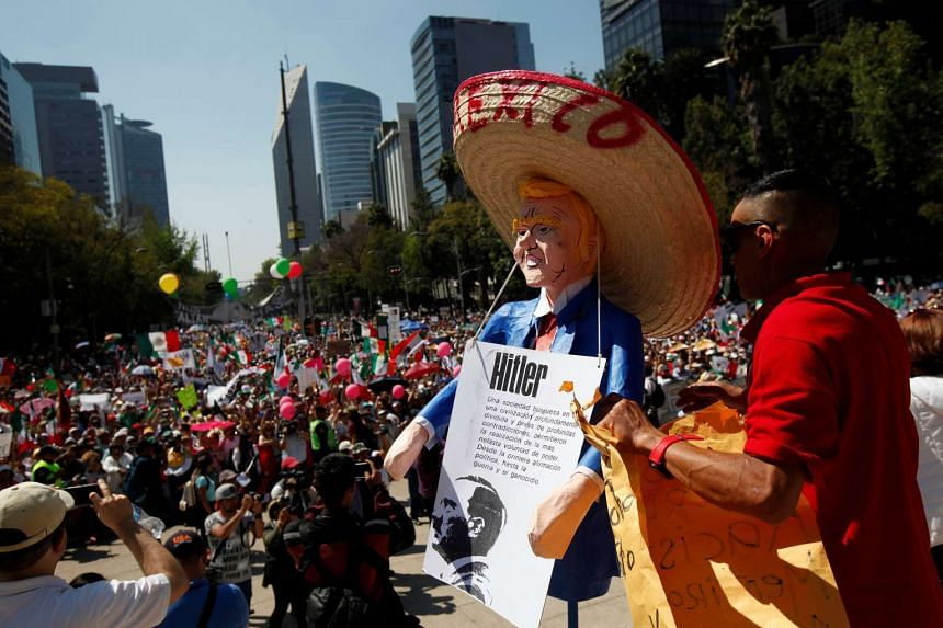 A man holds an effigy of US President Donald Trump wearing a Mexican hat during a march to protest against Trump's proposed border wall and to call for unity, in Mexico City, Mexico, on Feb 12, 2017.