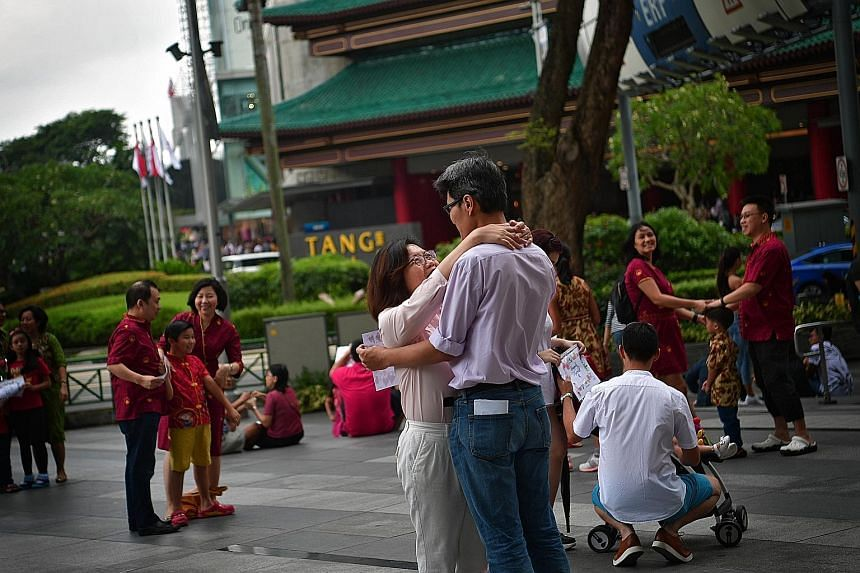 """A married couple caught in an embrace during a """"freeze flash mob"""" event in Orchard Road on World Marriage Day yesterday. To celebrate marriage in a unique way, about 350 people, including couples and families with children, gathered outside Ion Orcha"""