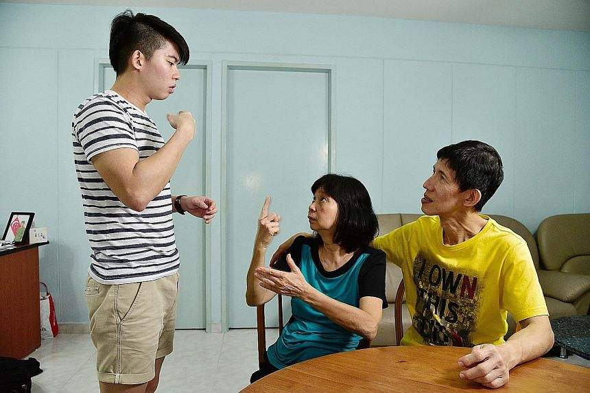 Mr Quek conversing in sign language with his parents, who missed his scholarship presentation ceremony because of their job schedules. He wants to create a device that can interpret sign language by detecting hand movements using a video camera and t