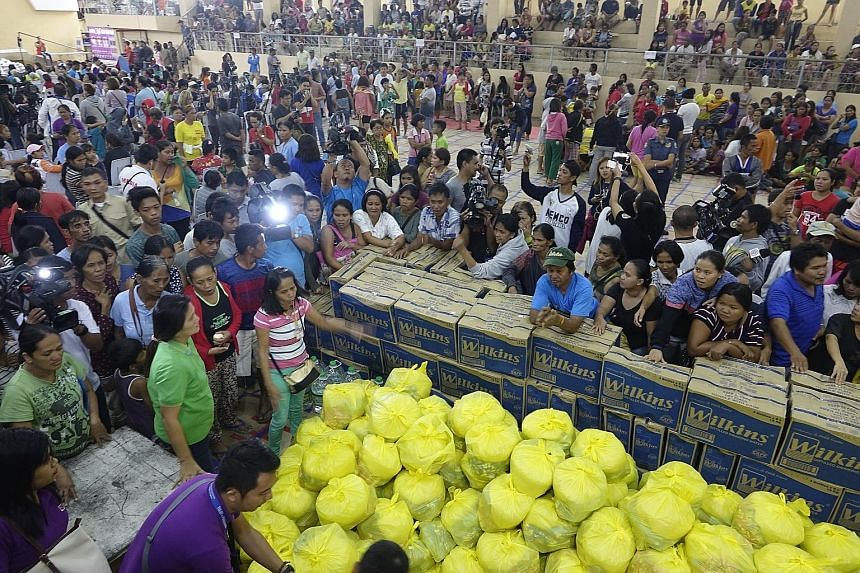 Villagers in Surigao collecting emergency relief items yesterday. The authorities have placed Surigao City under a state of emergency to hasten relief efforts.