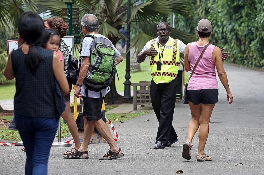 Security personnel informing visitors to the Gardens yesterday that Upper Palm Valley Road was closed as workers were still clearing the 40m-tall heritage tree that fell last Saturday.