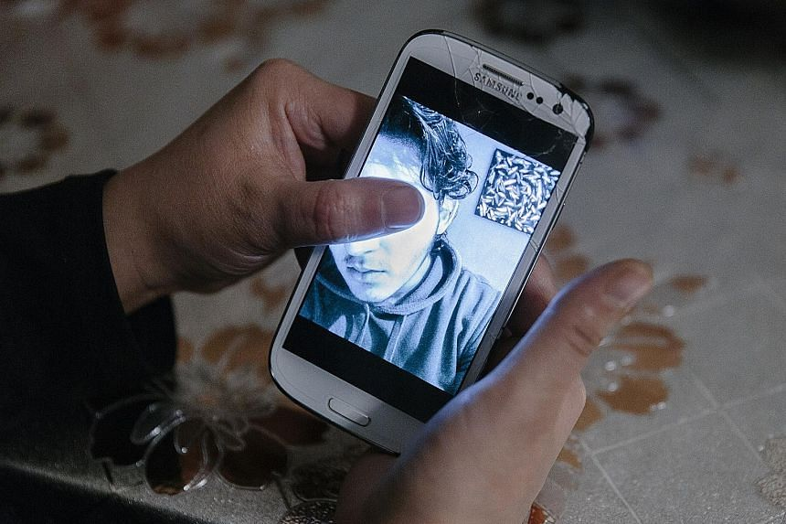A boy charged over a bomb attack at a Sikh temple in Essen, in a photo displayed on his mother's phone.