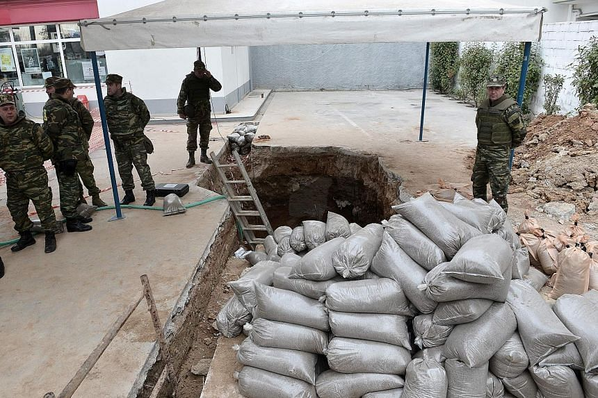 Greek military personnel at the site where a World War II bomb was discovered in Kordelio, Thessaloniki, before the bomb was deactivated yesterday. The explosive was uncovered during excavation works at a petrol station. Up to 72,000 residents were t
