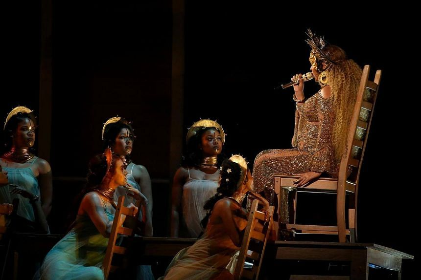 Singing seated on a chair and surrounded by floating petals, Beyonce also appeared in video projections wearing a gold-chain string bikini.