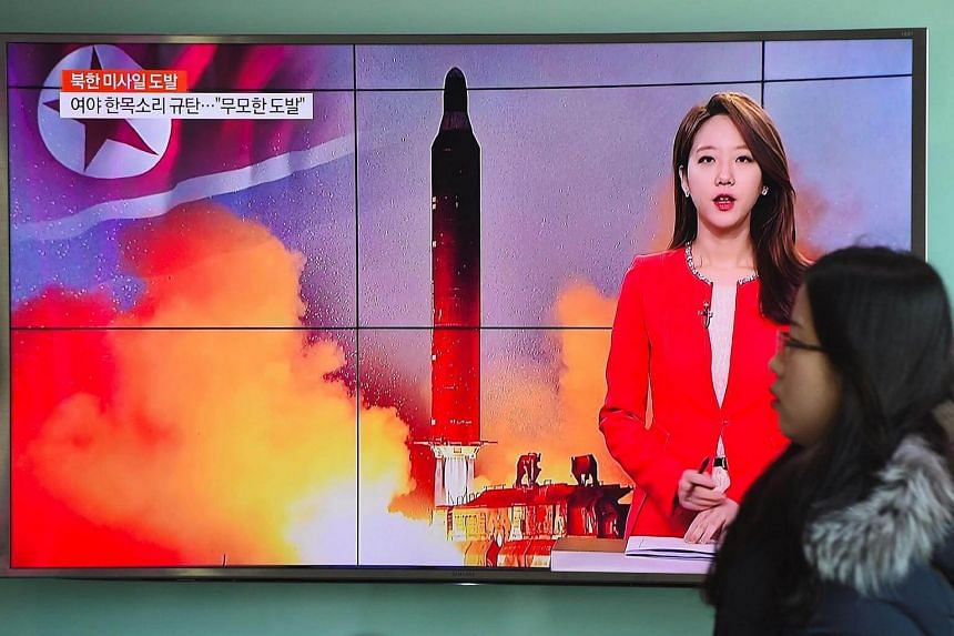 A woman walking past a television screen showing file footage of North Korea's missile launch at a railway station in Seoul, on Feb 12, 2017.