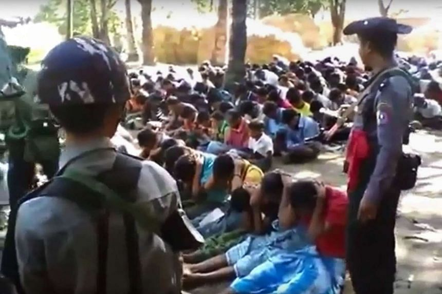 A screen grab taken on Jan 4, 2017, from a YouTube video originally taken by Myanmar Constable Zaw Myo Htike (not pictured) shows policemen standing guard around Rohingya minority villager seated on the ground in the village of Kotankauk during a pol