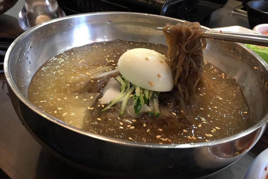 The Naengmyeong (S$15) is cold noodles glistening in a light beef broth that's so cold, it's like a shimmering jelly soup with slices of Korean pear floating in it.