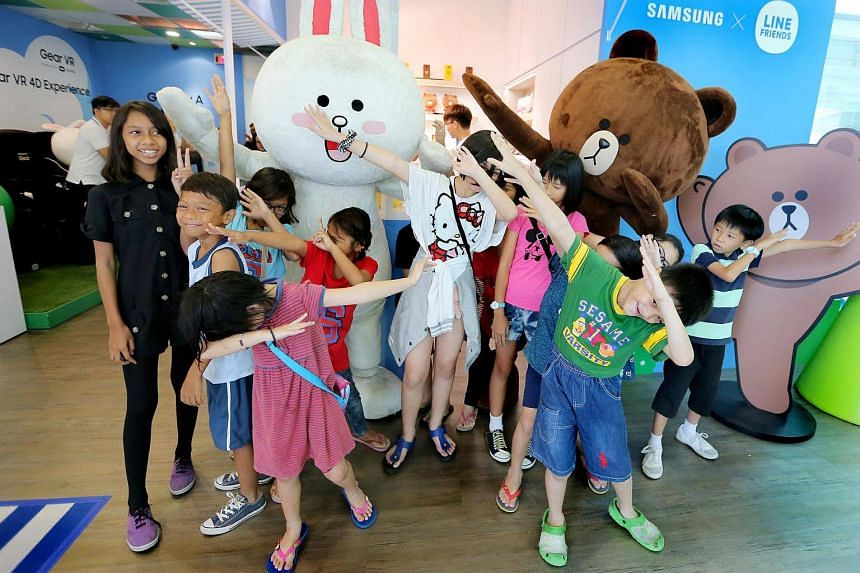 Students from low-income families posing with Line mascots at the Samsung experiential theme zone at the Westgate mall on Feb 11, 2017.