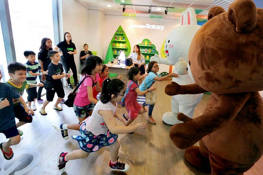 Students from low-income families rushing to hug Line mascots at the Samsung experiential theme zone at the Westgate mall on Feb 11, 2017.