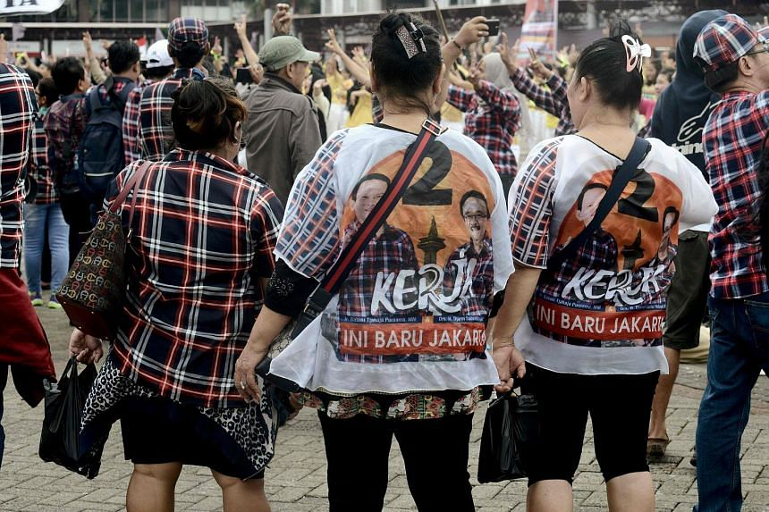 Supporters wearing T-shirts in support of Jakarta's governor Basuki Tjahaja Purnama and his running mate Djarot Saiful Hidayat during their final campaign rally in Jakarta, on Feb 11, 2017.