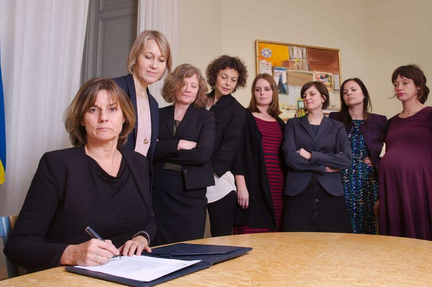 Swedish Environment Minister and Deputy Prime Minister Isabella Lovin (left) signs a referral of Swedish climate law, binding all future governments to net zero emissions by 2045 at the ministry in Stockholm on February 1, 2017. The bill signing was
