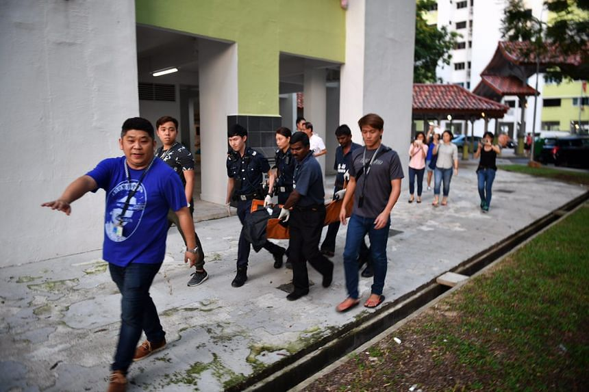 Police officers carrying away the body of a woman who was found dead in a flat in Tampines, on Feb 13, 2017.