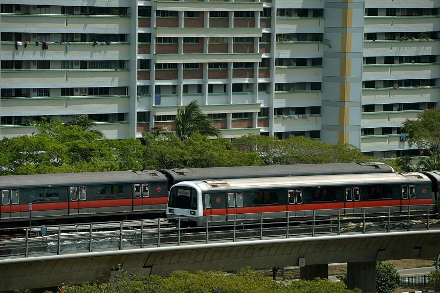 Two SMRT trains passing each other along the North-South Line near the Woodlands MRT station.