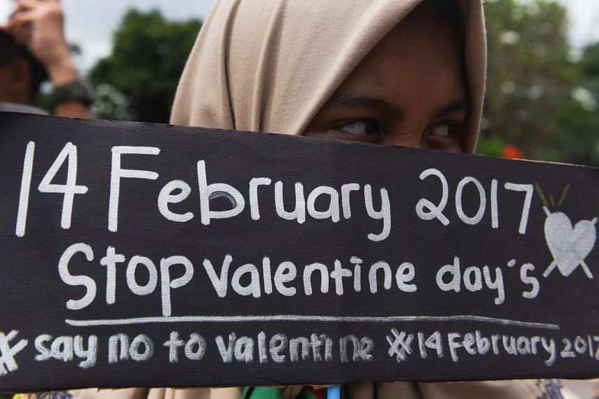 A student holding a placard during a protest against Valentine's Day in Surabaya, Indonesia, on Feb 13, 2017.