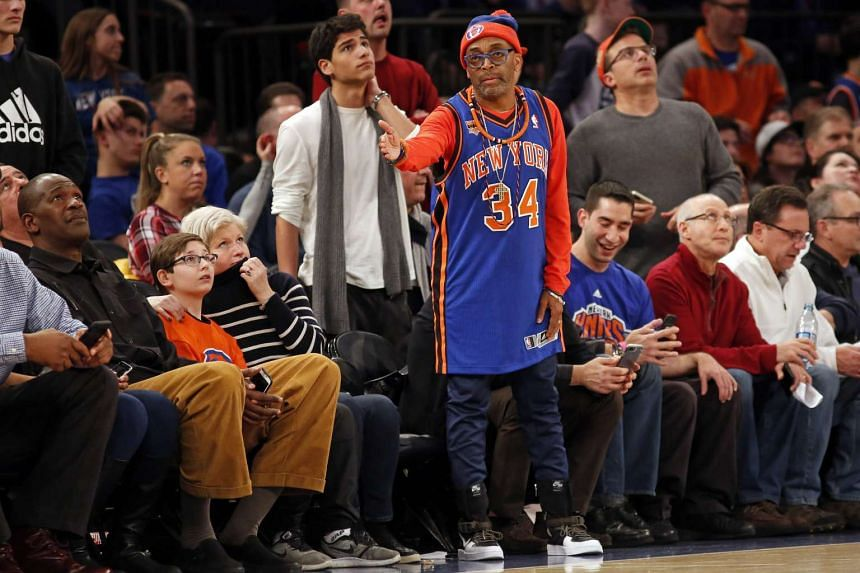 Wearing a Charles Oakley jersey director Spike Lee reacts during the second half against the San Antonio Spurs at Madison Square Garden.