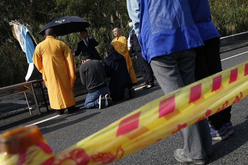 Relatives of bus accident victims conduct a ritual at the bus crash site on a highway in Taipei, Taiwan, on Feb 14, 2017.
