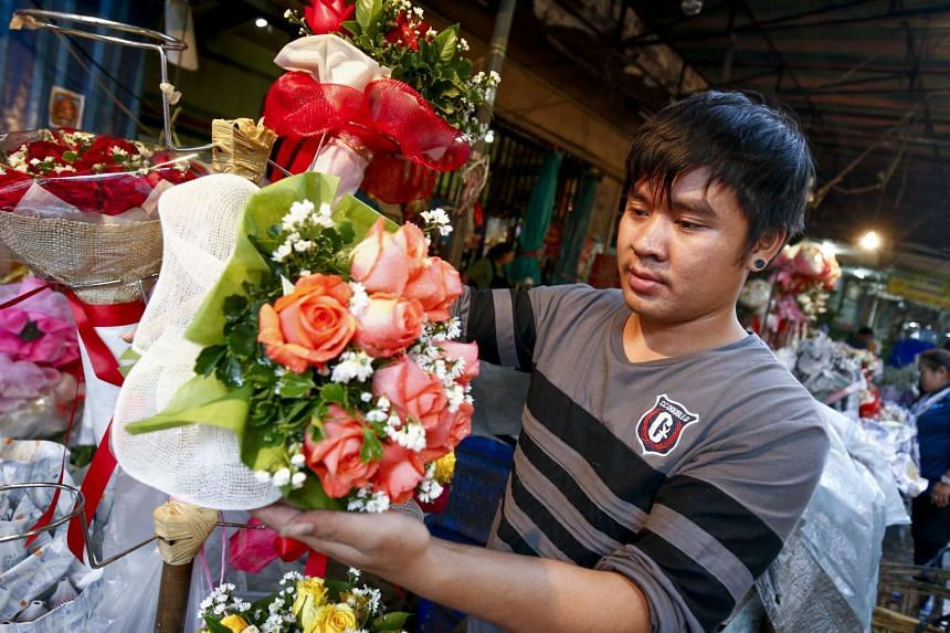 A man preparing a bouquet of roses at a flower market in Bangkok on Feb 14, 2017.