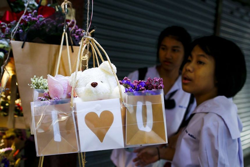 Thai students looking at flower arrangements for sale at a flower market in Bangkok on Feb 14, 2017.