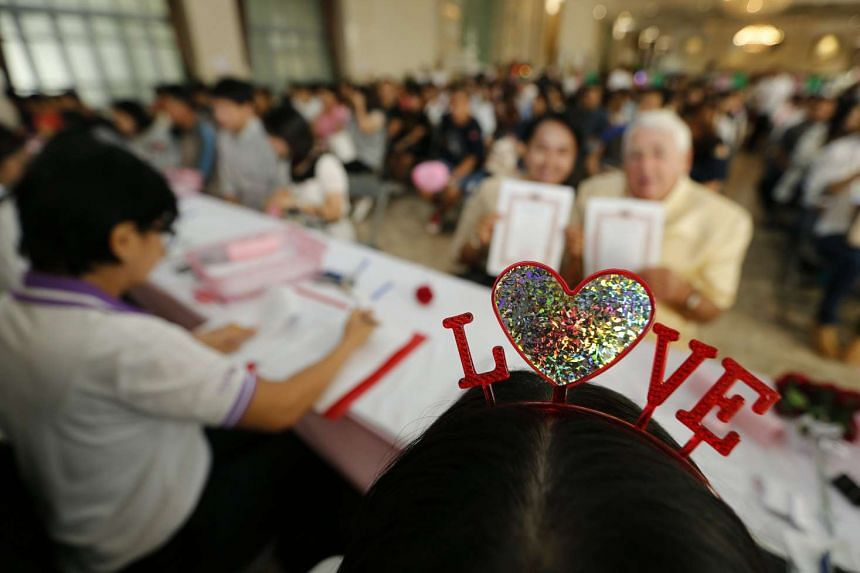 Thai couples attending a group marriage licence ceremony at the Bang Rak district office in Bangkok on Feb 14, 2017.