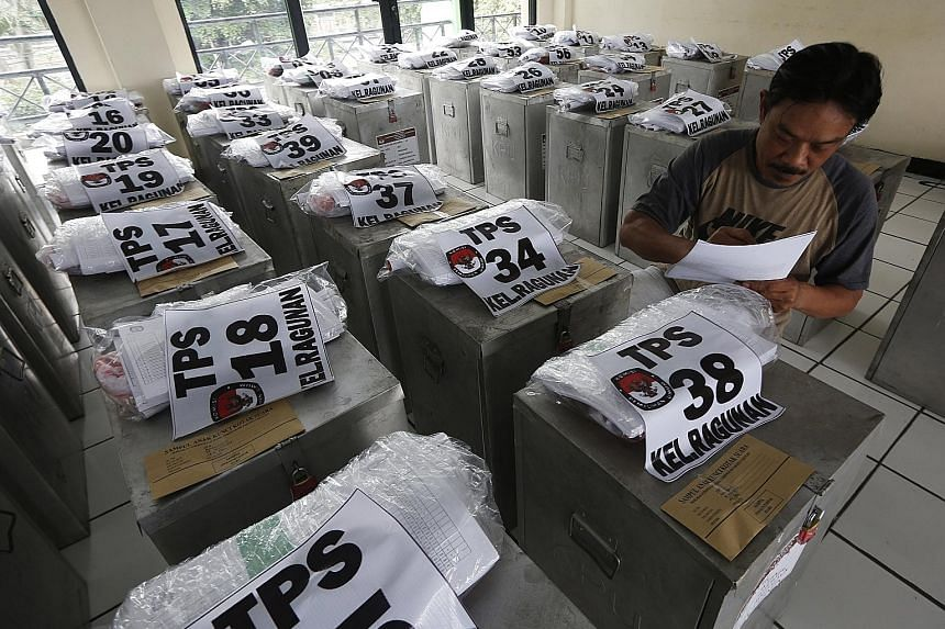Ballot boxes being checked in Jakarta yesterday before the polls.