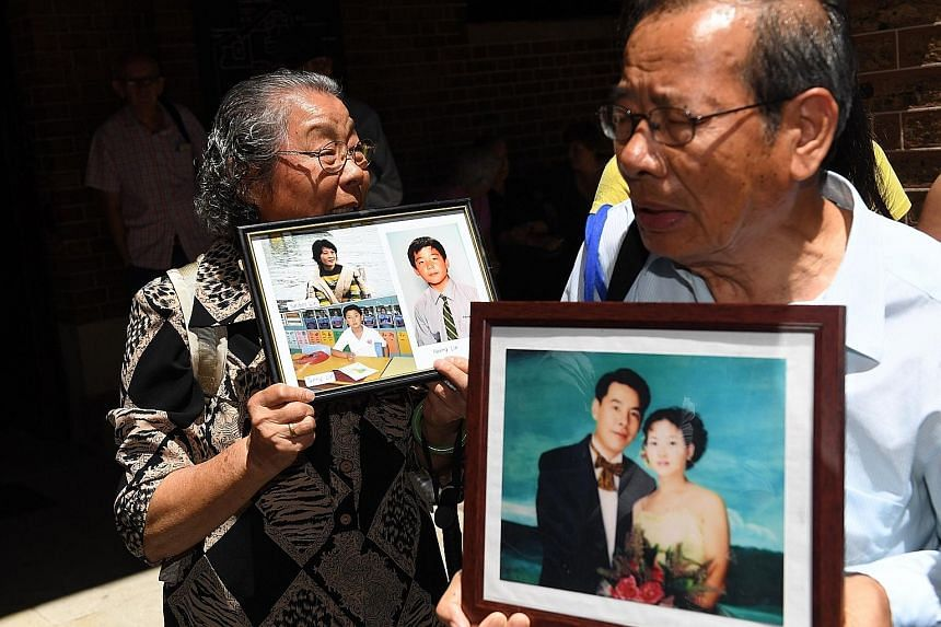 Xie being led away yesterday, after being found guilty of murdering five of his relatives. He plans to appeal. The parents of Mr Norman Lin with portraits of the slain family members outside the New South Wales Supreme Court in Sydney yesterday.