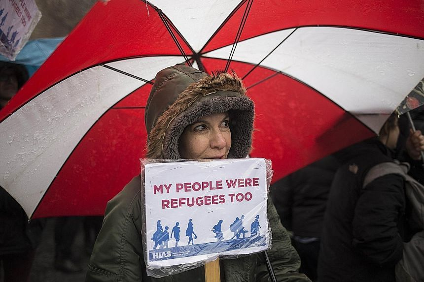 A member of Jewish refugee group Hebrew Immigrant Aid Society rallying against Mr Trump's travel ban in New York City on Sunday.