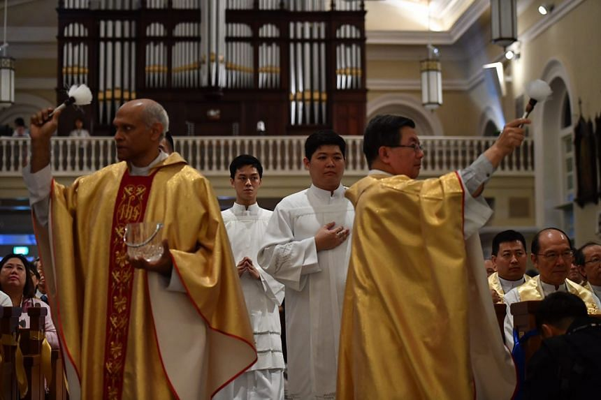 Priests sprinkling holy water during a mass for the dedication of the Cathedral of the Good Shepherd, on Feb 14, 2017.