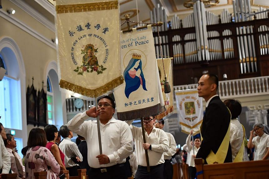 People carrying the banners of other Catholic churches, during the dedication ceremony at the Cathedral of the Good Shepherd, on Feb 14, 2017.