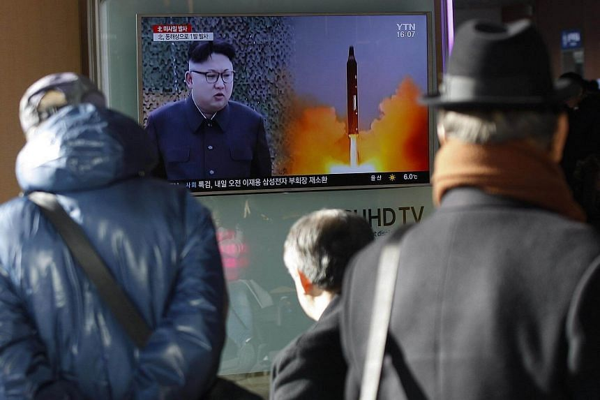 South Koreans watching a television news broadcast showing an image of Kim Jong Un at a station in Seoul, South Korea.