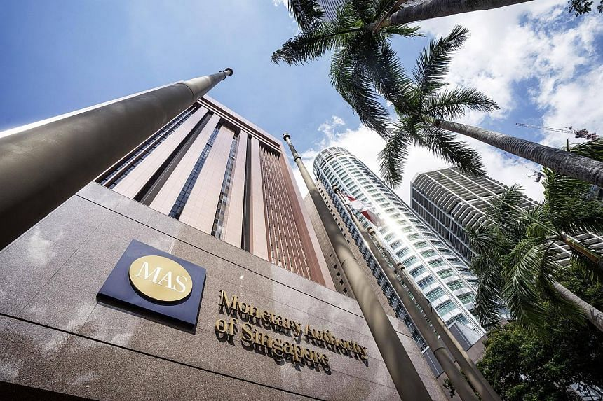The Singapore national flag flies next to signage for the Monetary Authority of Singapore.