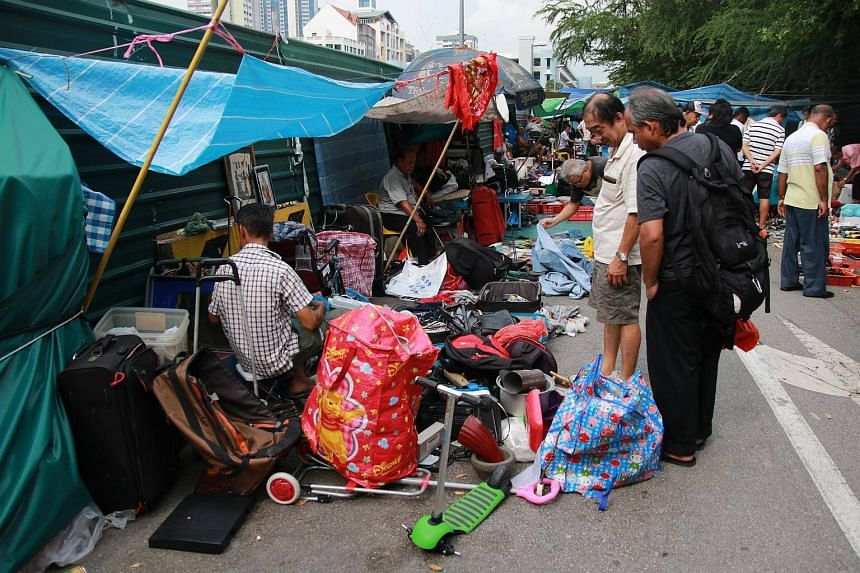 People looking at second-hand or used merchandise at the Sungei Road flea market.