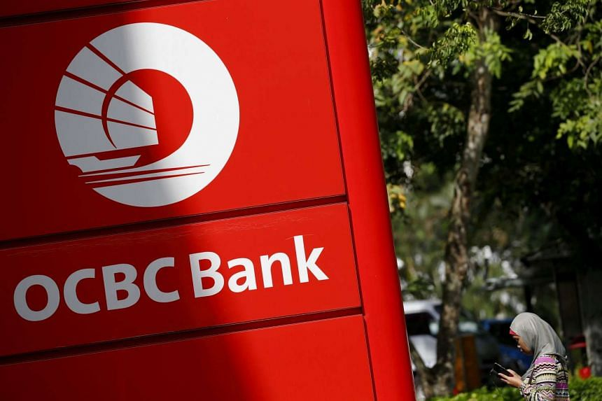 A woman walking past an Oversea-Chinese Banking Corporation (OCBC) branch in Singapore.