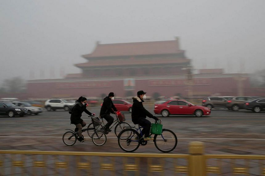 People wearing masks cycle past Tiananmen Gate during the smog after a red alert was issued for heavy air pollution in Beijing, China, on Dec 20, 2016.