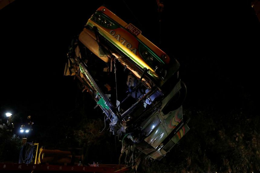 Cranes hoist the frame of a bus early this morning (Feb 14, 2017) which crashed after an accident on a highway in Taipei.