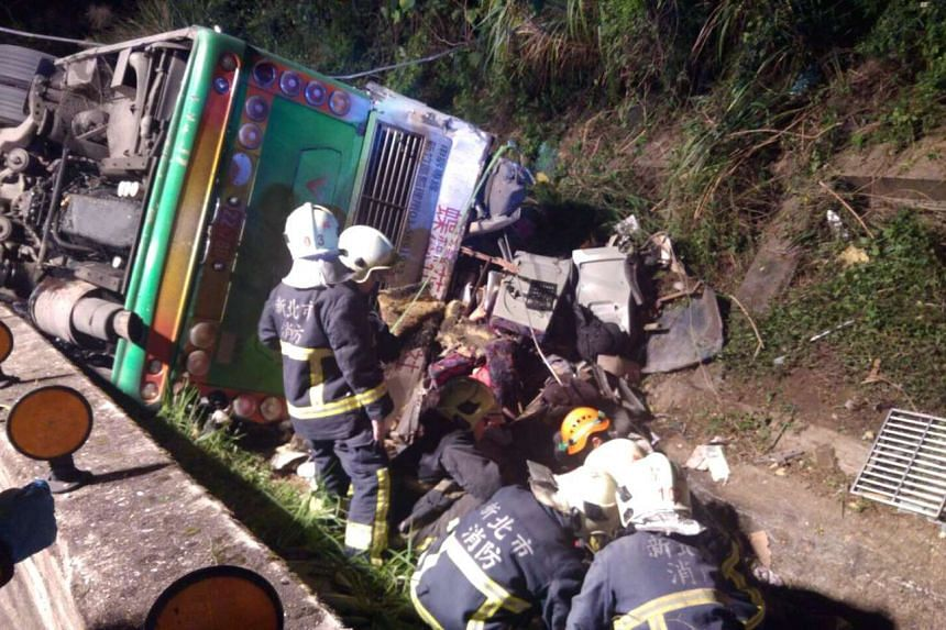 Rescuers tend to the injured beside a crashed tourist coach near Taipei, Taiwan, on Monday (Feb 13, 2017).