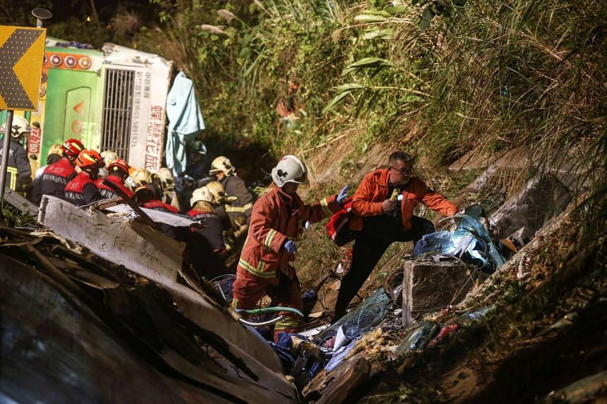 Rescuers recover bodies of victims from a bus crash site at a highway in Taipei on Monday night (Feb 13, 2017).