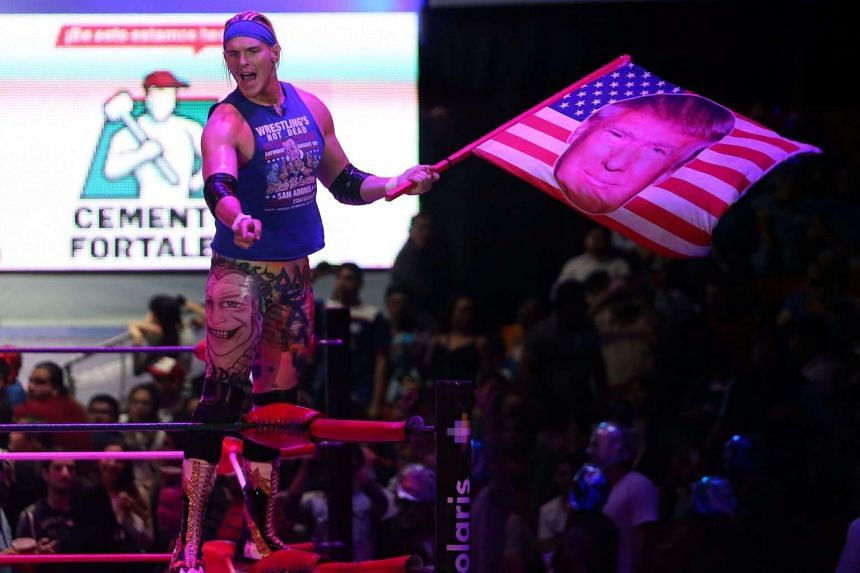 US wrestler Sam Adonis waves a flag with US President Donald Trump's face during a wrestling match in Mexico City, Mexico, on Sunday (Feb 12, 2017).