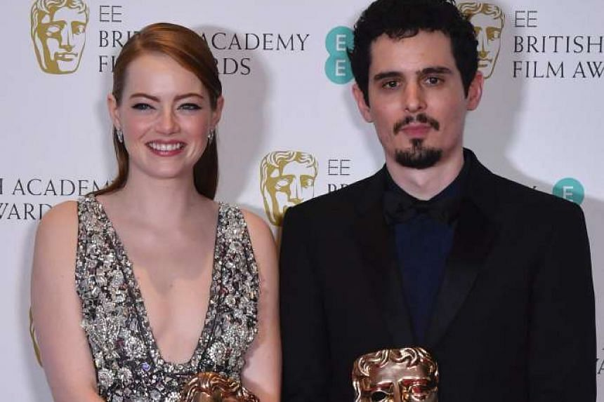 La La Land's Emma Stone and Damien Chazelle with their best actress and best director trophies.