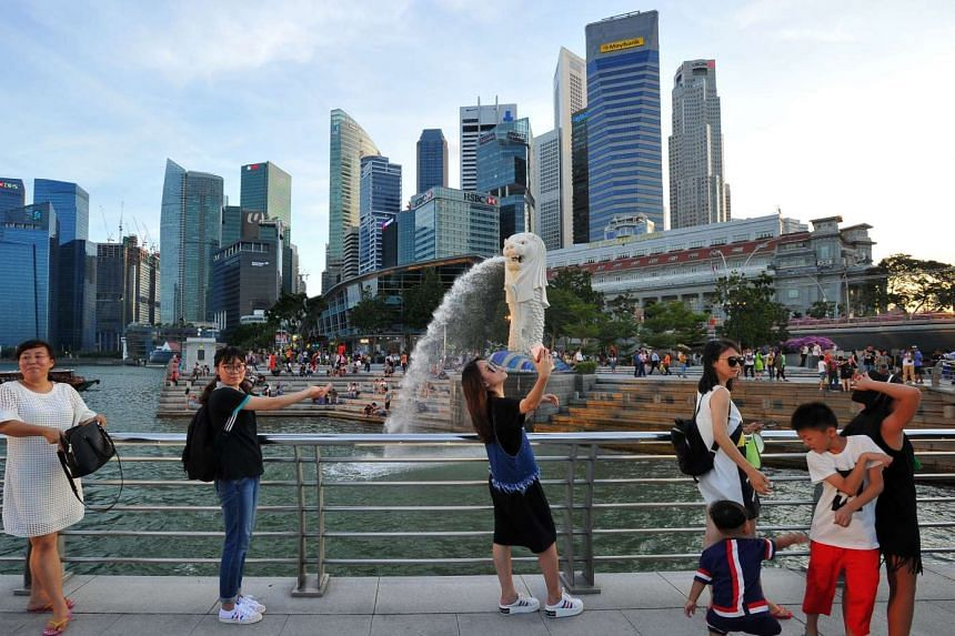 Tourists taking photos at the Merlion Park with the skyline of the Central Business District in the background.