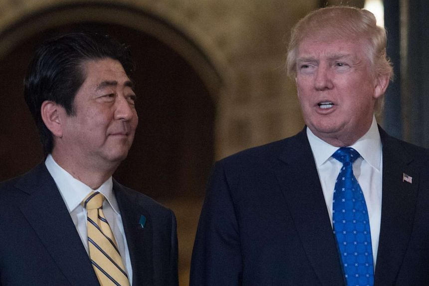 US President Donald Trump and Japanese Prime Minister Shinzo Abe posing for photos at Trump's Mar-a-Lago resort in Palm Beach, Florida.