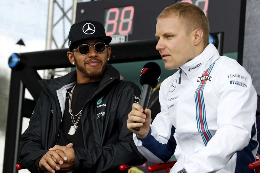 Lewis Hamilton (left) watches as Valtteri Bottas speaks to fans at the Australian Grand Prix in Melbourne in March 2016.