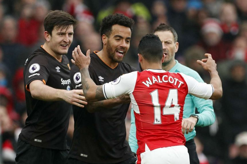 Arsenal's Theo Walcott clashes with Hull City's Harry Maguire and Tom Huddlestone as referee Mark Clattenburg looks on.