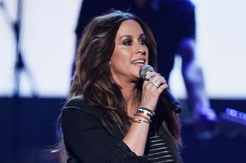 Alanis Morissette performing onstage during the 2015 American Music Awards.