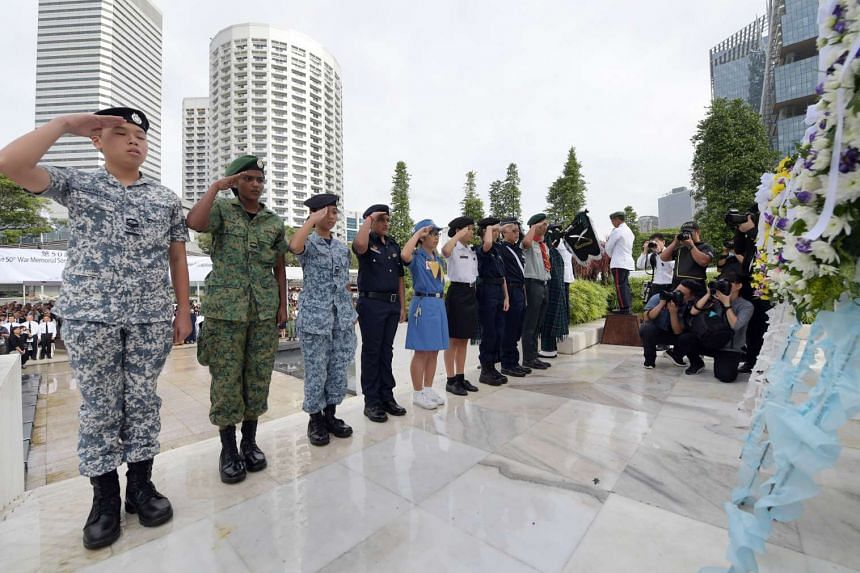 In front of the Memorial to the Civilian Victims of the Japanese Occupation, school uniformed groups representatives from the National Cadet Corps, National Police Cadet Corps, National Civil Defence Cadet Corps, The Boys' Brigade in Singapore, Gir