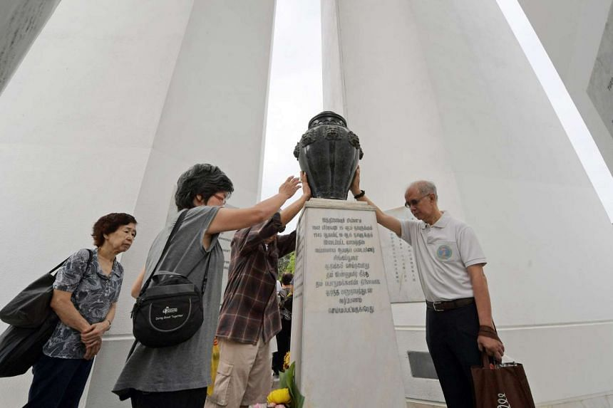Visitors lay their hands on the urn at the Memorial to the Civilian Victims of the Japanese Occupation.