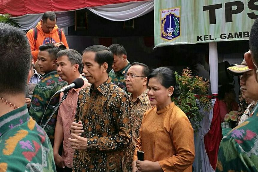 President Joko Widodo and First Lady Iriana seen at a polling station in Gambir, after casting their votes.